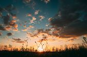 Sun At Sunset Sunrise Sky. Bright Dramatic Sky With Clouds. Yellow, Orange, Blue Colors. Dark Ground poster