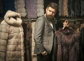 Man With Beard And Mustache Holds Fur Coat. Winter Clothing Concept. Guy Holds Furry Coat In Shop Wi poster