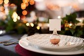 Close up of Christmas table setting with bauble name card holder arranged on a plate and green and r poster