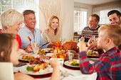 Multi-Generation Family Sitting At Table Making A Toast Whilst Eating Thanksgiving Meal At Home Toge poster