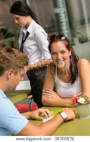 Couple at cafe man looking at menu woman smiling restaurant
