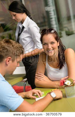 Couple at cafe man looking at menu woman smiling restaurant