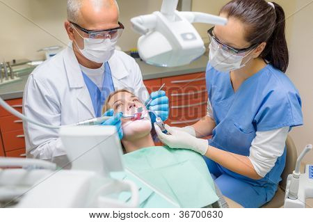 Professional dentist and nurse doing operation on female patient