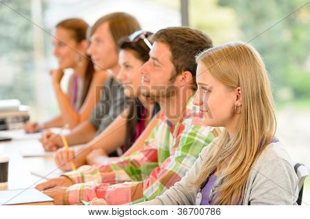 High-school students listening to lesson in class campus college teens