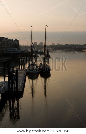 Pair Of Sail Boats Reflecting Into Thames As The Sun Rises