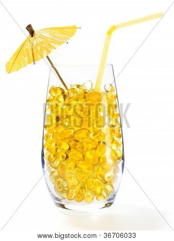 Healthy Vitamin Cocktail: Yellow Oil Pills In Translucent Glass With Straw And Umbrella