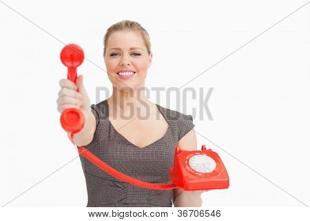 Smiling woman showing a retro phone against white background