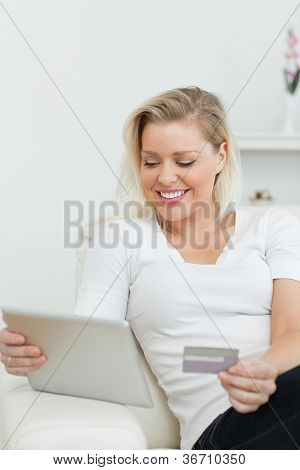 Casual woman using a tablet pc for e-commerce on a sofa