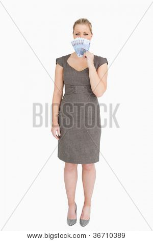 Woman hiding her mouse with euro banknotes against white background