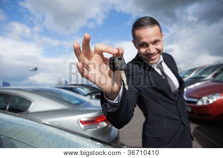 Happy dealer holding car keys outdoors