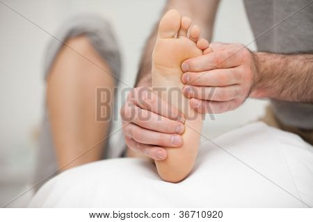Chiropodist palpating the sole of the foot of a patient in his office