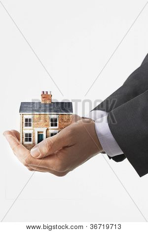 Business man holding model house
