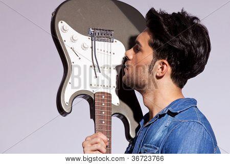 guitarrista de joven enamorado de su guitarra eléctrica sobre fondo gris