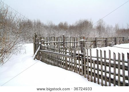 old wooden fence on winter snow