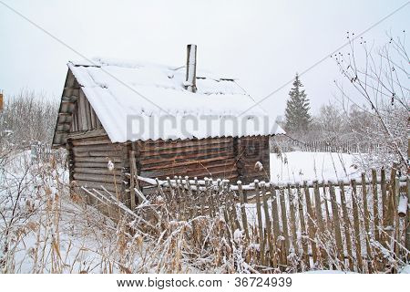 old rural wooden house amongst snow