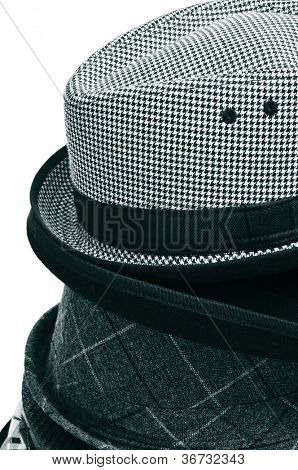 closeup of a pile of different hats a white background