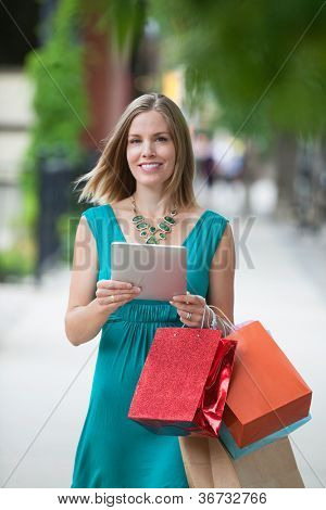 Portrait of a happy young woman with shopping bags and digital tablet on sidewalk