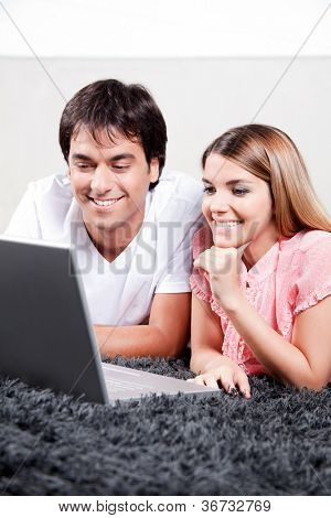 Happy young couple using laptop.