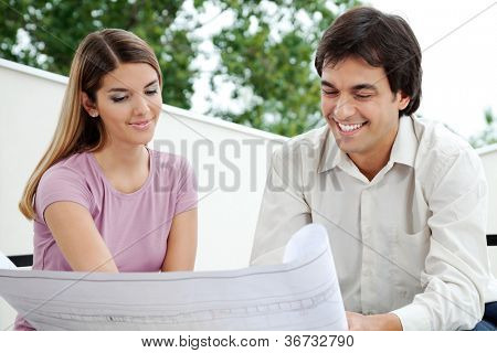 Young female with male architect looking at blueprint