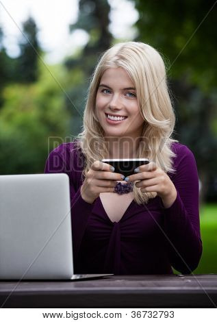 Portrait of smiling young female holding smart phone