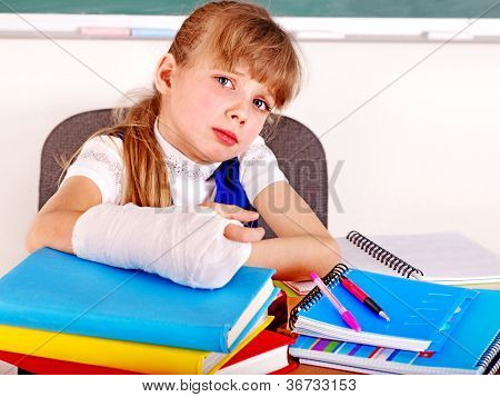 Disabled sad child with broken arm in classroom.