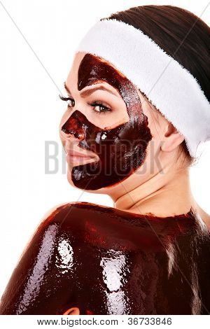Young woman having chocolate facial mask. Isolated.