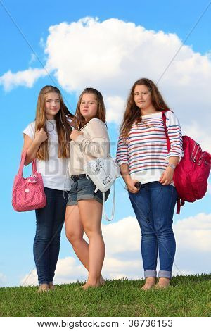 Three girls stand with bags on grass at background of blue sky. Two left girls listen to music from one headphone drops.
