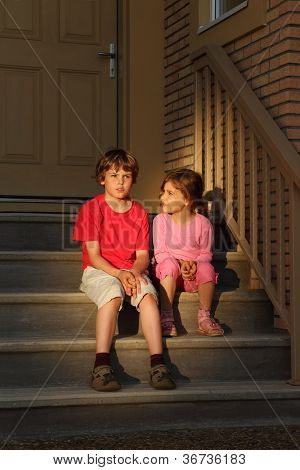 Serious boy and girl sit on stairs near door and look into distance at evening.
