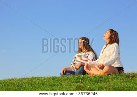 Two young girls sit and meditate at green grass at background of blue sky.
