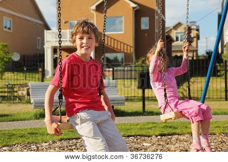 Little girl and boy sit on swing near cottage at sunny day. Focus on boy.