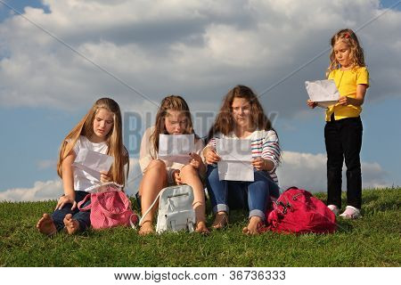 Three girls sit on grass and read something and little girl stand near them and read too at background of blue sky.