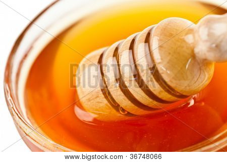 Honey dipper outgoing a bowl against a white background