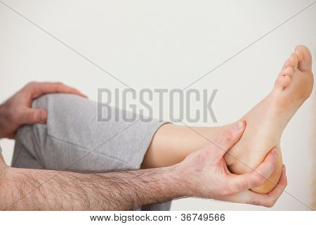 Chiropractor holding the heel of a patient in a room