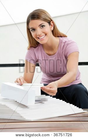 Portrait of beautiful female architect working on a tangible model