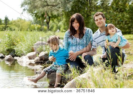 Happy similing young family sitting by lake