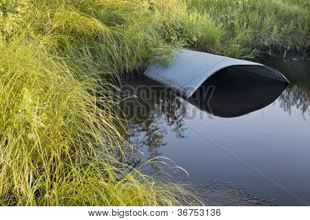 green meadow and irrigation ditch with culvert