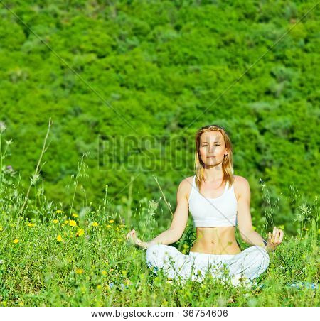 Photo of beautiful woman doing yoga exercise outdoors, mental health, healthy lifestyle, cute young lady sitting in lotus pose, pretty girl is engaged in fitness in park over green trees background