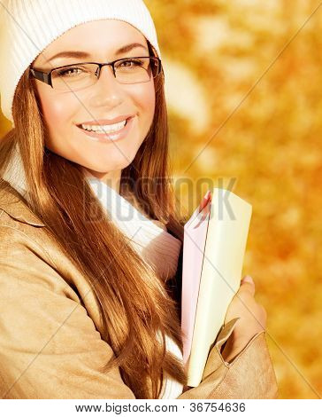 Image of cheerful student girl spend leisure in autumn park, closeup portrait of beautiful teen hold textbook in hands, cute schoolgirl wearing warm hat with scarf and glasses, back to school