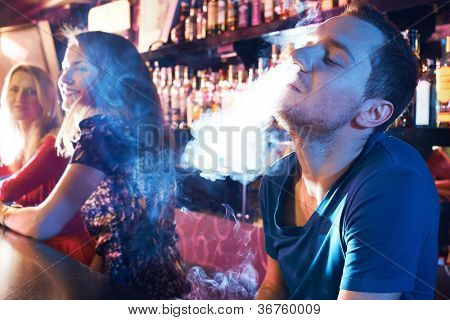 Portrait of young man letting smoke out of nostrils while smoking hookah
