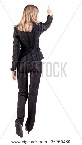 Back view of  business woman walking and pointing. young businesswoman in black suit. Rear view people collection.  backside view of person.  Isolated over white background.