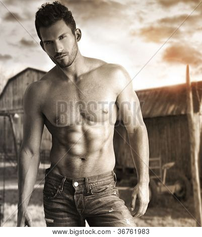 Sepia toned portrait of a hunky male model in nostalgic outdoor rustic setting
