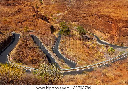 curves winding road high view in red mountains in gran canaria