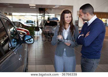 Woman explaining something to a man in a dealership