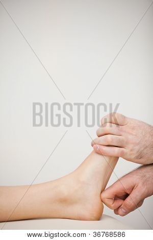 Chiropodist using his index finger to massage a foot in a medical room