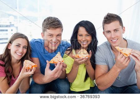 A group of friends about to eat their pizza while they look at the camera