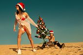 stock photo of toboggan  - Sexy Santa helper  pulling Santa on a sled with Christmas tree at the beach - JPG