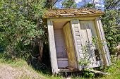 stock photo of outhouses  - Old wooden outhouse with two separate seats leaning backward and a porcelain door handle on one of the doors - JPG
