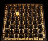 stock photo of unicity  - A white pawn is the only one surrounded by the other black pawns