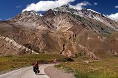 image of aconcagua  - Woman cycling on the empty road from Mendoza in Argentina to Valparaiso in Chile - JPG