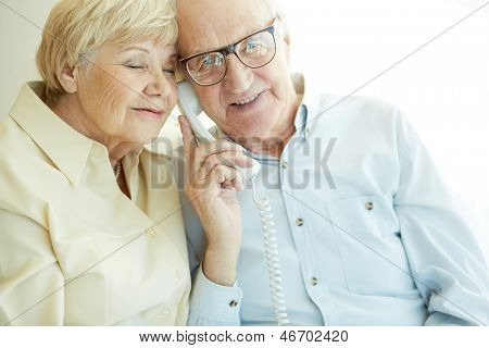 Portrait of elderly man looking at camera awhile talking on the phone with his wife near by